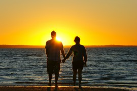paar hält händchen am Strand im Sonnenuntergang Honeymoon